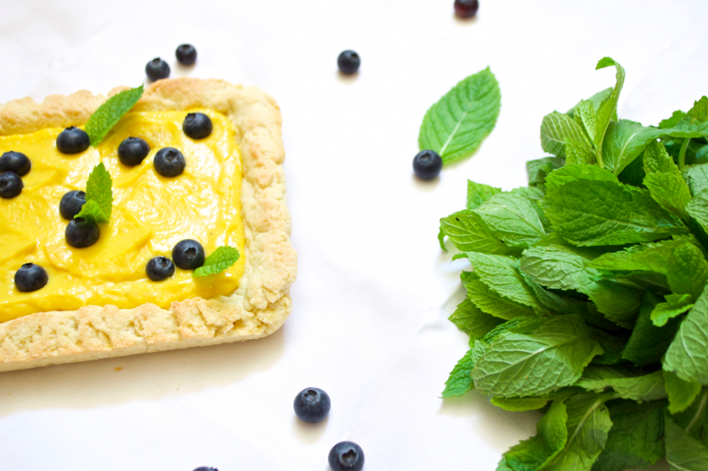 white chocolate mango curd tart with mint and blueberries